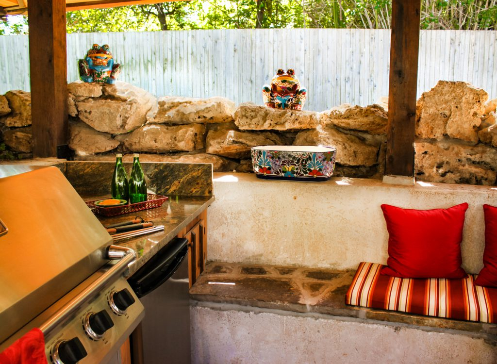 Outdoor barbeque area with stone benches and cushions and electric grill